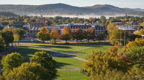 An image from Baker Tower overlooking the Green on an autumn day as fog rises in the mountains behind town.