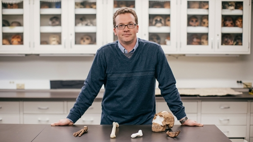 Jeremy DeSilva standing behind a table with 3D printed versions of the discovered homo naledi fossils