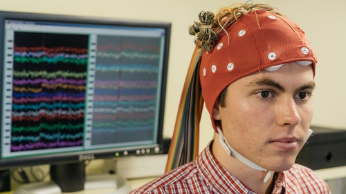 a research assistant wearing a red cap with wires connected to it