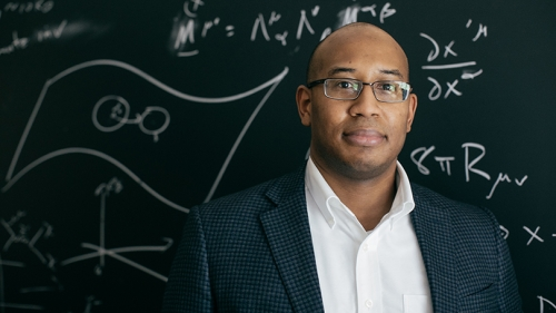 Devin Walker standing in front of a chalk board with scientific equations written on it
