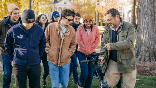 Associate Professor Jesse Casana with a number of students outside