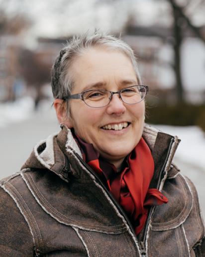 Picture of Michelle Warren, short grey hair, glasses. brown jacket, red scarf in winter