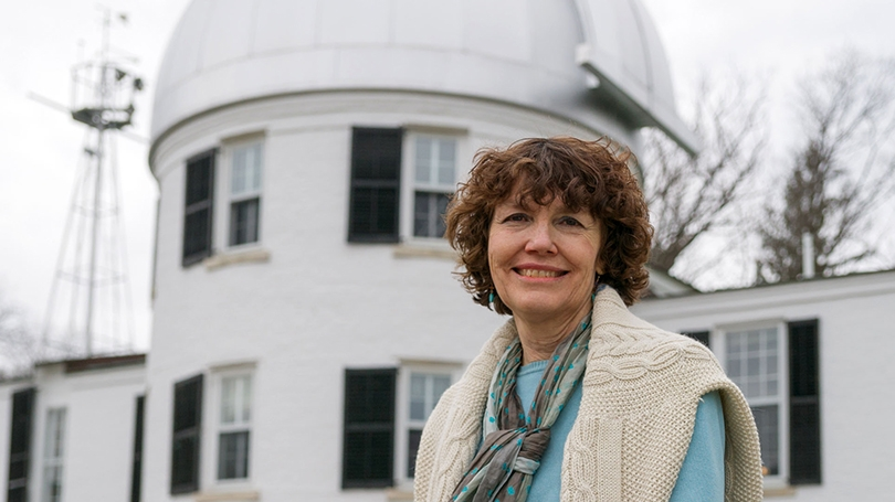 Mary Hudson standing in front of the observatory building