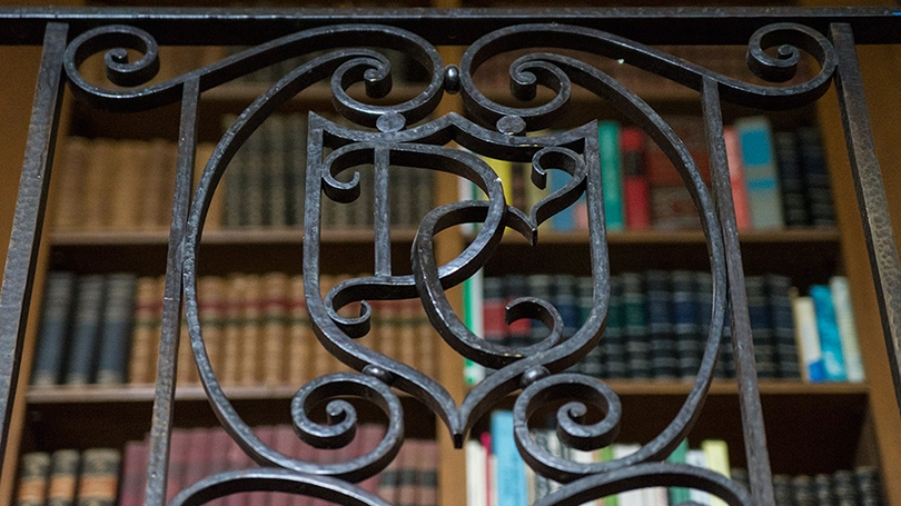 an iron bannister in Baker Library with the letters D and C worked in a fancy script